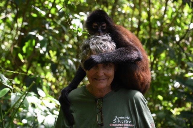 Woman looking at camera with spider monkey on shoulders